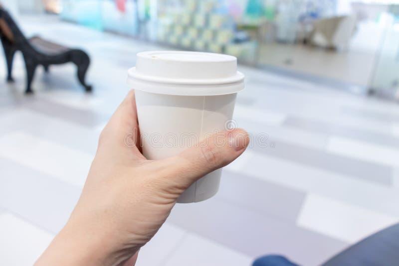 Main de femme tenant la tasse de disposadle blanc de café de papier photos libres de droits