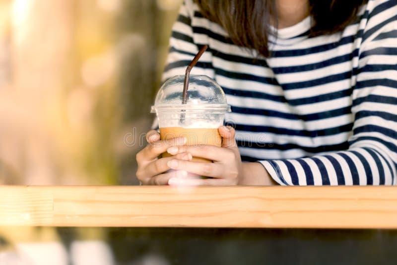 Main de femme tenant la tasse en plastique de café de glace dans le café images stock