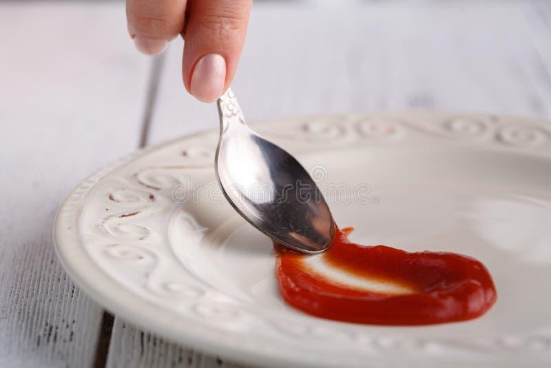 Main de femme tenant la tasse de ketchup de pomme de terre image stock