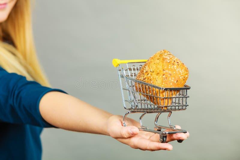 Main de femme tenant le caddie avec du pain photos stock
