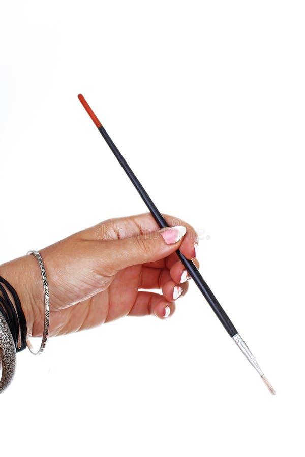 Main de femme tenant le pinceau sur le fond blanc d'isolement de coupe-circuit Photo de studio avec l'allumage de studio facile à images libres de droits