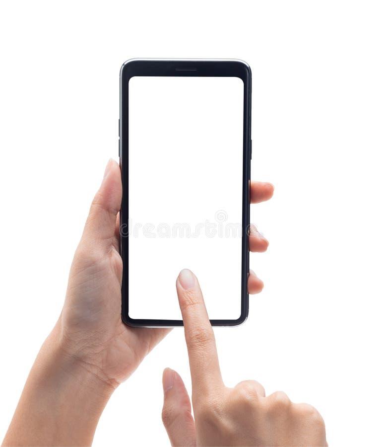 Main de femme tenant le smartphone noir et le touchant sur l'écran vide d'isolement sur le fond blanc avec le chemin de coupure photos libres de droits