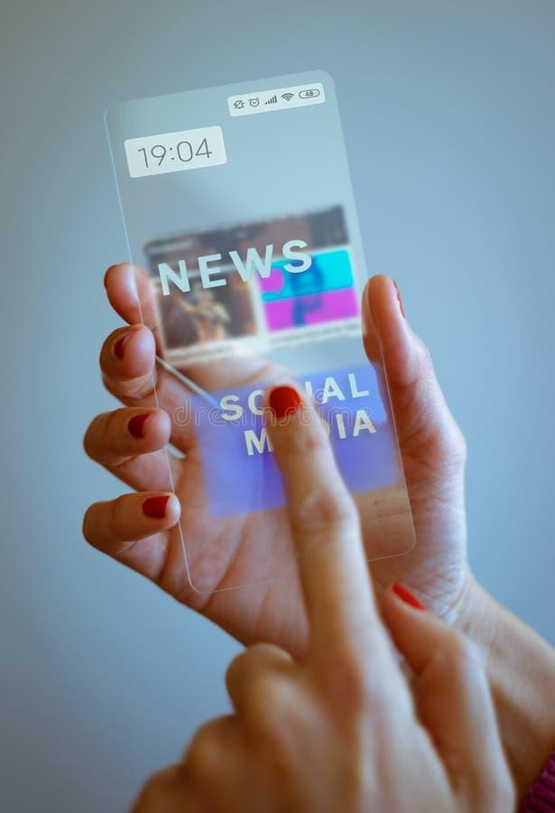 Main de femme tenant le smartphone transparent et touchant l'écran images libres de droits