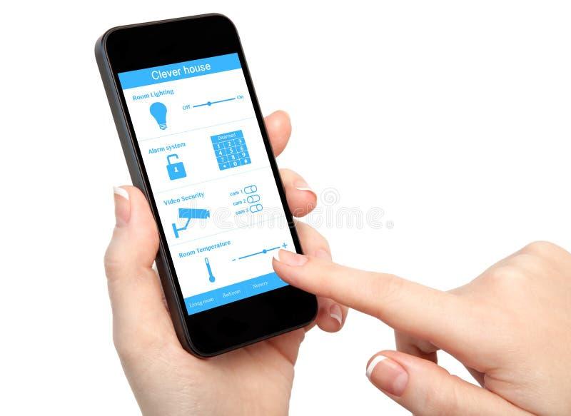 Main de femme tenant le téléphone avec la maison intelligente de système photos stock