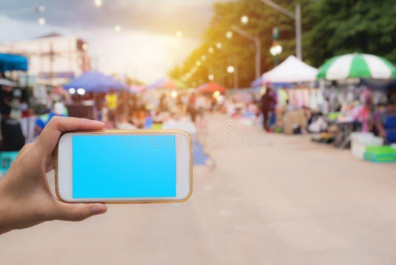 Main de femme tenant le téléphone intelligent dans la tache floue d'achats de marché en plein air photos stock