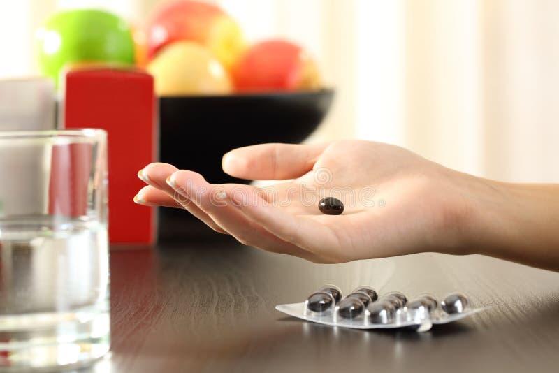 Main de femme tenant une pilule de complexe de vitamine photographie stock libre de droits