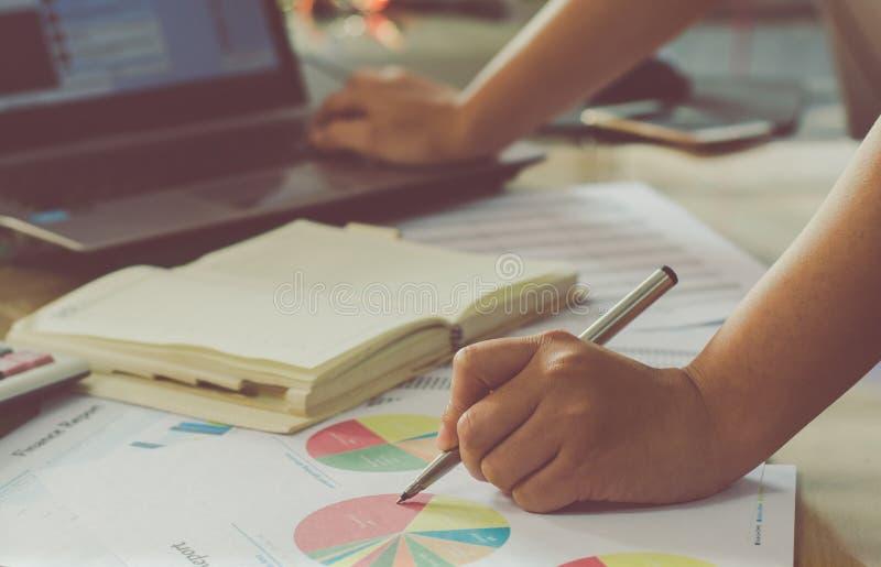 main de femme utilisant le stylo se dirigeant sur le compte rendu succinct et et employant la La photo stock