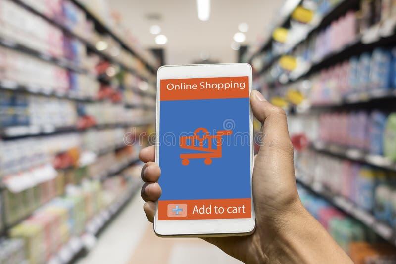 Main de femme utilisant le téléphone intelligent à l'achat au magasin en ligne dans la tache floue photos libres de droits