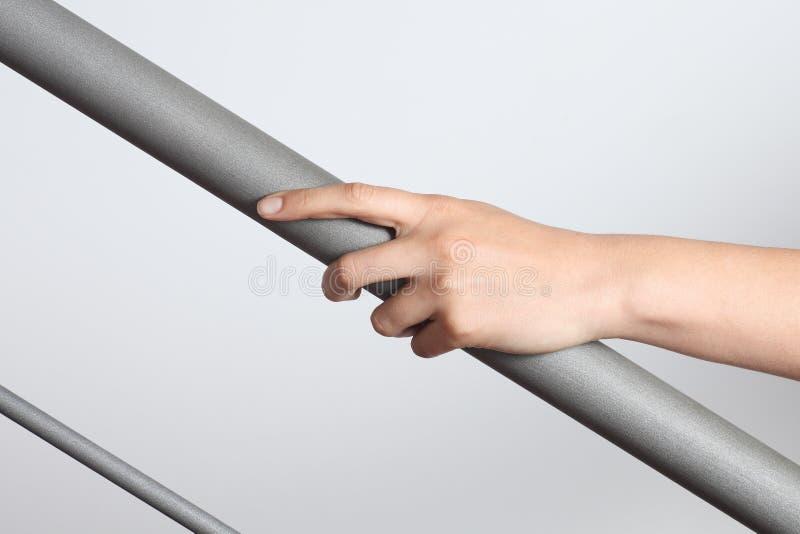 Main de femme utilisant une balustrade à aller en haut images stock