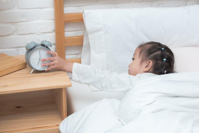 Main de fille asiatique atteignant pour arrêter le réveil sur le lit pendant le matin images stock