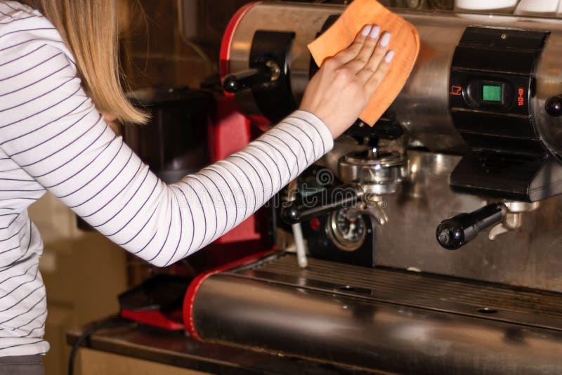 Main de fille avec du chiffon nettoyant la machine sale de café d'expresso dans une cuisine de barre image stock