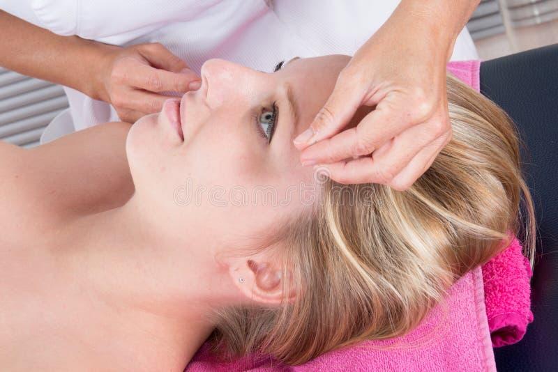 Main de fille effectuant la thérapie d'acuponcture sur la tête au salon de station thermale image stock