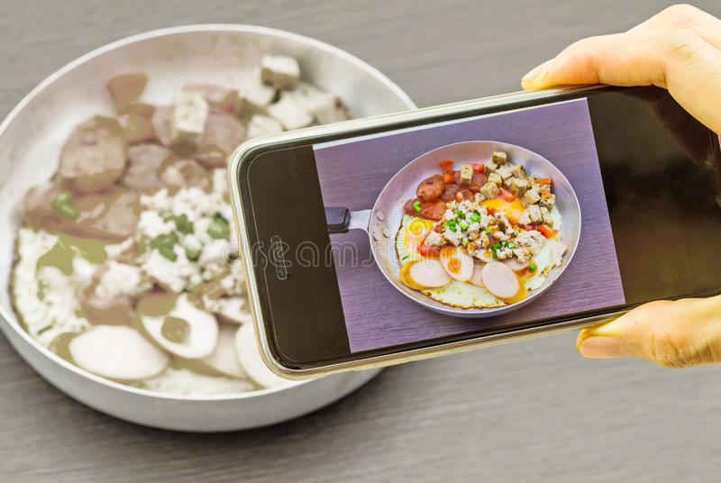 Main de fille prenant des photos à un téléphone portable dans la casserole de l'Indochine photo libre de droits