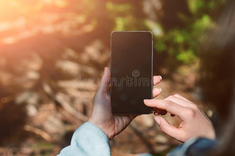 Main de fille tenant le téléphone portable d'écran vide dans le jardin de forêt tropicale image stock