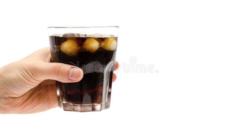 Main de fille tenant le verre de rhum avec le coke D'isolement sur le fond blanc copiez l'espace, calibre image libre de droits
