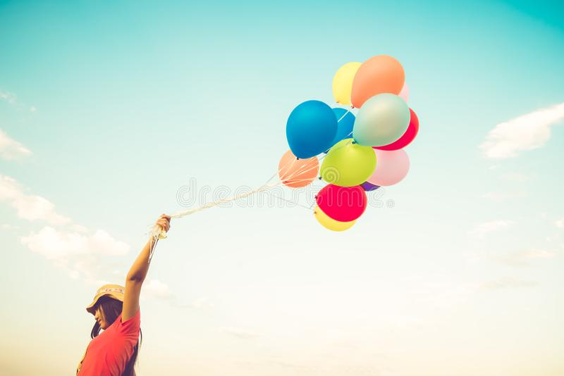 Main de fille tenant les ballons multicolores photo stock