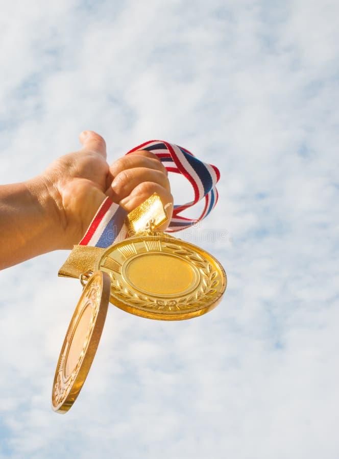 main de gagnant augmentée et tenante deux médailles d'or contre le ciel bleu photographie stock libre de droits