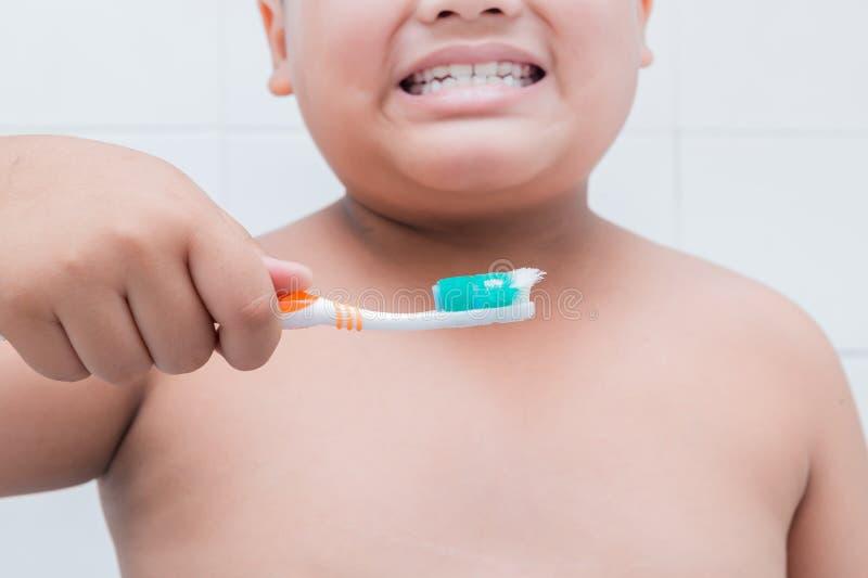 Main de garçon tenant la vieille brosse à dents photographie stock