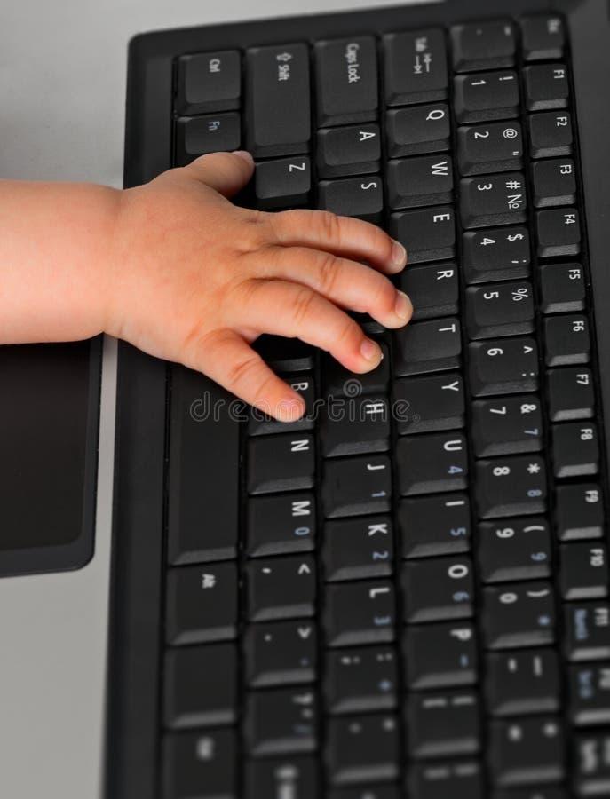 Main de gosse sur un clavier d'ordinateur portatif photographie stock libre de droits
