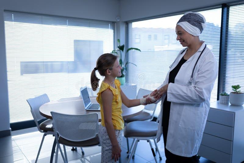 Main de interaction et de examen de docteur féminin mûri de fille dans la clinique photographie stock libre de droits