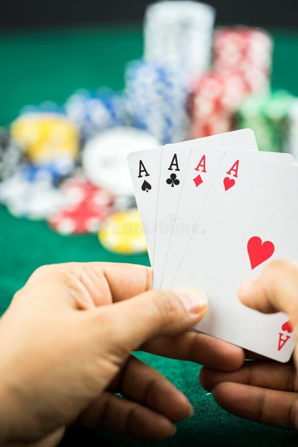 Main de jeu tenant la meilleure série de carte de jeu et les puces d'argent images stock
