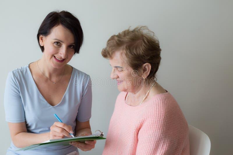 Main de jeune femme écrivant l'enquête femelle pluse âgé de client image stock