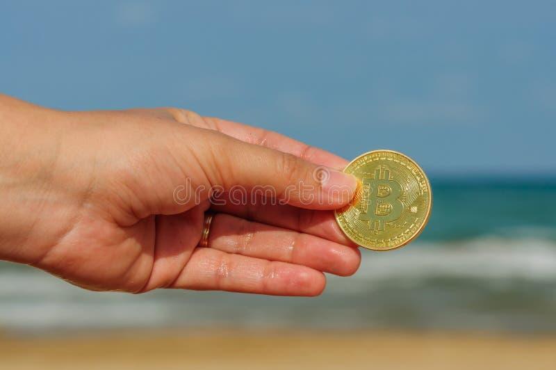 Main de jeune femme avec la pièce de monnaie physique de peu dans la plage, concept de pièce de monnaie de peu, commerce électron photos libres de droits