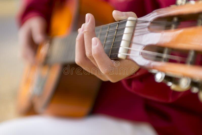 Main de jeune fille jouant sur la guitare acoustique Plan rapproché photos stock