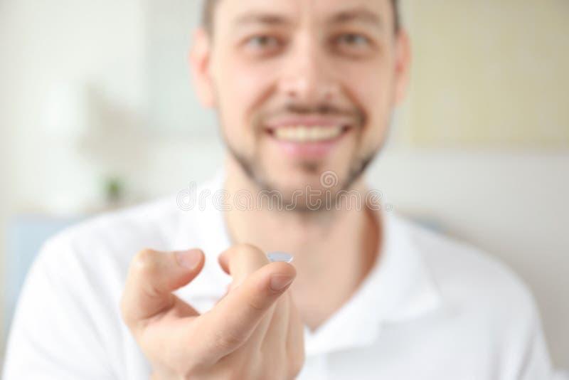Main de jeune homme avec le verre de contact, photo libre de droits