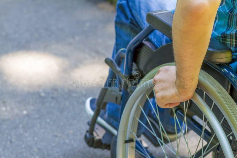 Main de jeune homme sur la roue du fauteuil roulant photos libres de droits
