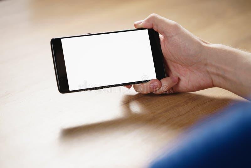 Main de jeune homme tenant le smartphone avec l'écran blanc vide image libre de droits