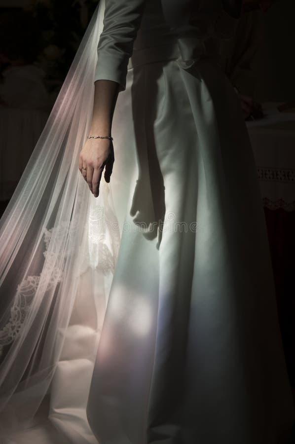 Main de jeune mariée et bijoux dans l'église, lumière de coloration photos stock