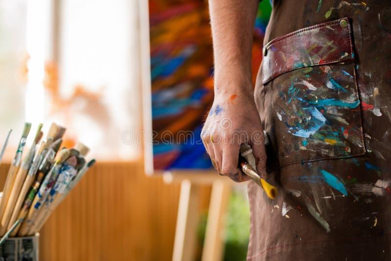 Main de l'artiste contemporain en tablier tenant un pinceau tout en travaillant en studio photographie stock