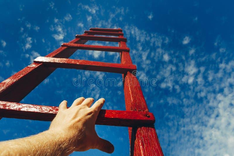 Main de l'homme atteignant pour l'échelle rouge menant à un ciel bleu Concept de croissance de carrière de motivation de développ photo stock