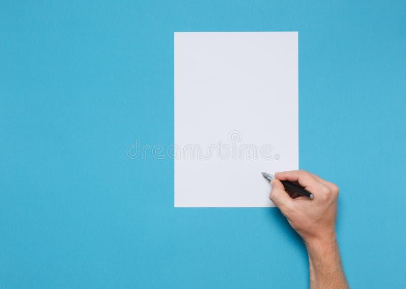 Main de l'homme avec le papier de Pen And Blank Sheet Of sur un fond bleu, vue supérieure Concept de minimalisme de créativité de image libre de droits