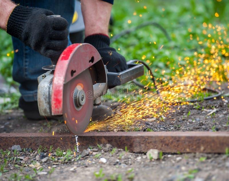 Main de l'homme avec l'outil en acier de coupeur sur le fond vert Le travailleur dehors, a coupé les rails en métal Processus ave photos libres de droits