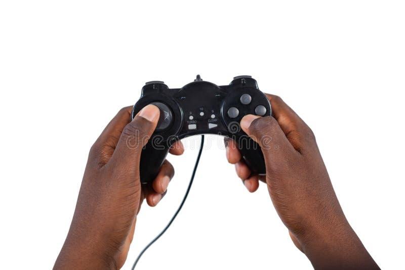 Main de l'homme jouant le jeu vidéo sur le fond blanc image libre de droits