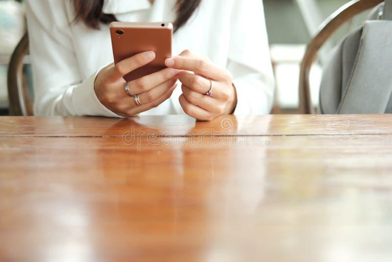 Main de la femme de l'Asie à l'aide du téléphone portable et se reposant en café de café images stock