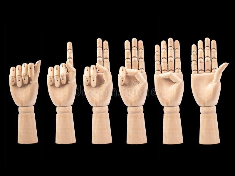 Main de la poupée en bois faire des doigts à compter les numéros 0 à 5 sur le bakground noir images libres de droits
