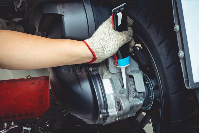 Main de mécanicien Check et d'huile à moteur Add à la moto, utilisations de mécanicien automobile de vérifier et système de moteu photos libres de droits
