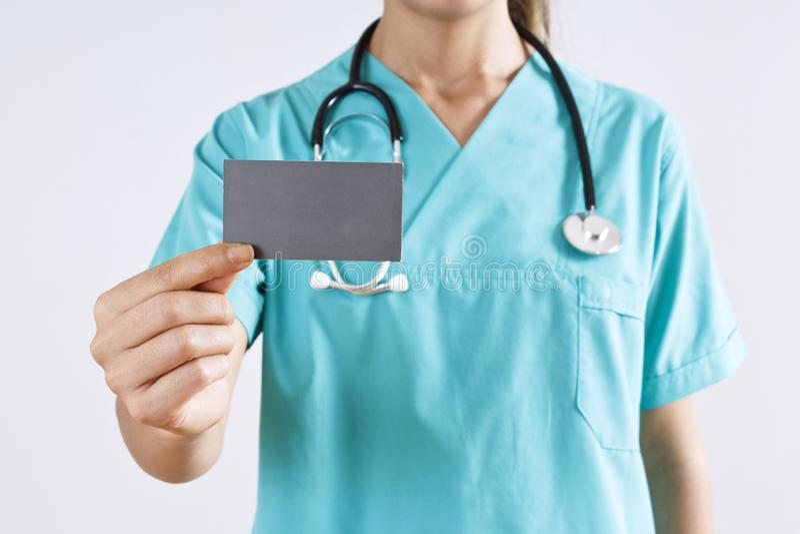 Main de médecin de femme tenant une carte vierge sur le fond gris images libres de droits