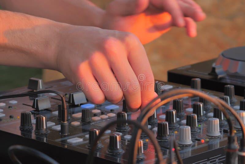 Main de mélangeur de contrôle de console de plaque tournante du DJ Le DJ jouant la musique photo stock
