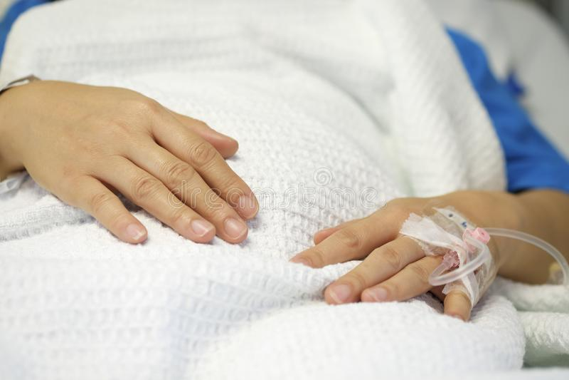 Main de patient hospitalisé insérée avec IV l'égouttement photo libre de droits