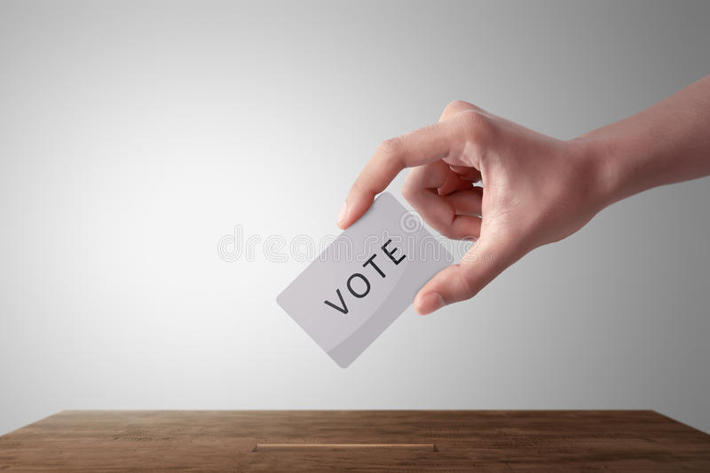 Main de personne donnant son vote dans une urne  images stock