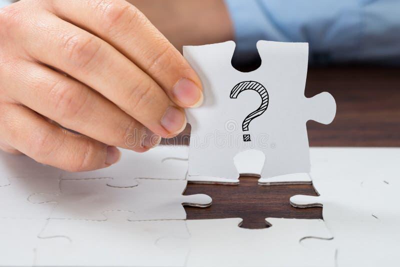 Main de personne tenant le puzzle avec le point d'interrogation images libres de droits