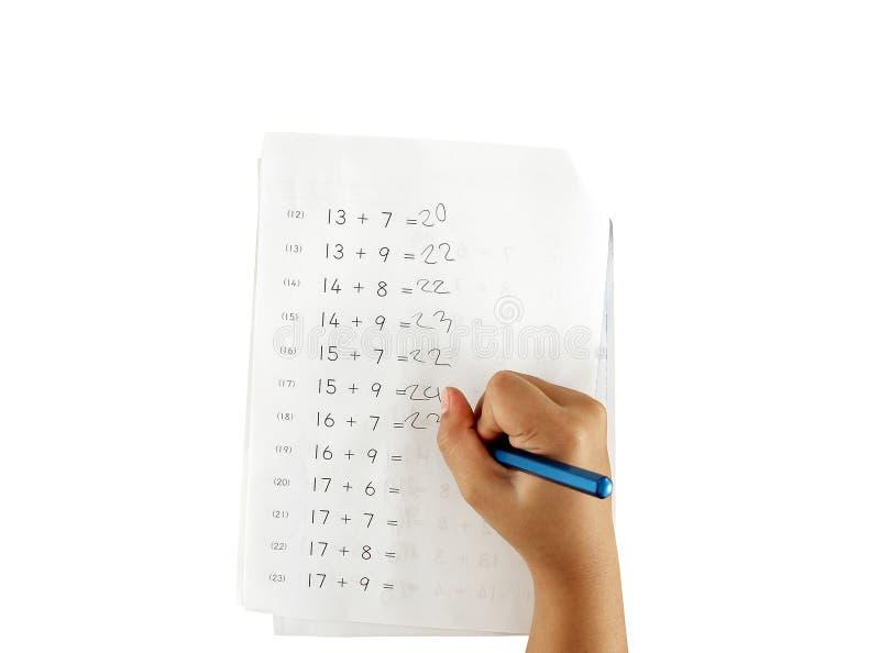 Main de petite fille faisant le travail de maths d'isolement sur le fond blanc photo stock