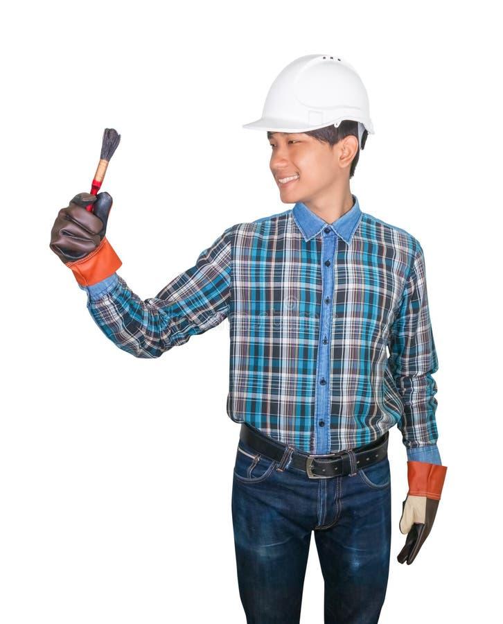Main de pinceau de participation d'ingénieur porter le bleu de chemise rayée et le cuir de gant avec du plastique blanc de casque images stock