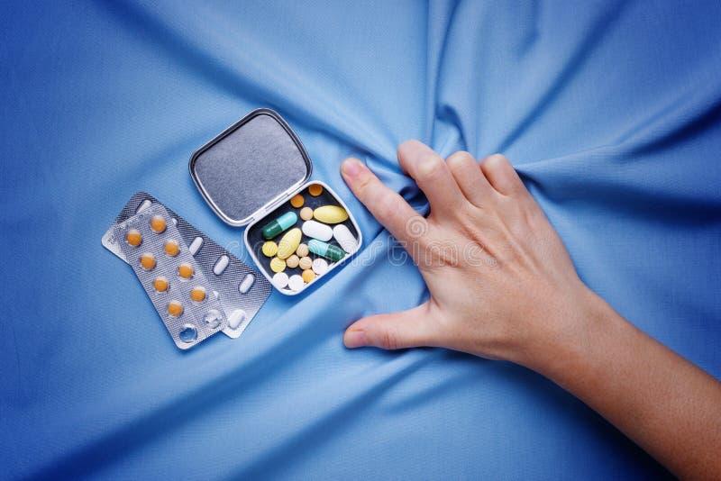 Main de plan rapproché essayant de prendre des pilules avec douleur et de souffrir photographie stock libre de droits