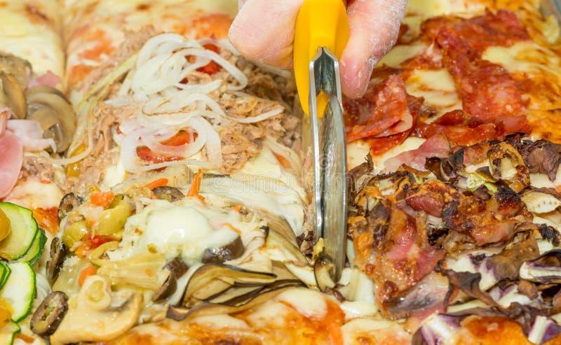 Main de plan rapproché de focacce de pizza de coupe de boulanger de chef à la cuisine Nourriture, cuisine italienne et concept de images libres de droits