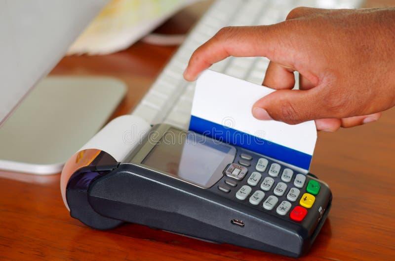 Main de plan rapproché frappant à toute volée la carte de crédit par le terminal de paiement se reposant sur la surface en bois image libre de droits